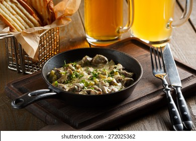 Roast with mushrooms, garlic sauce and chopped greens served in a frying pan on a wooden board, standing next to a glass of beer and golden pieces of bread