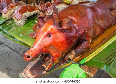 Roast pig head under sun picture. Fried meat and skin image. Barbecue pork on green table. Lechon or liempo - traditional dish of Philippines. Whole baked pig. Culinary photo from travel over Asia