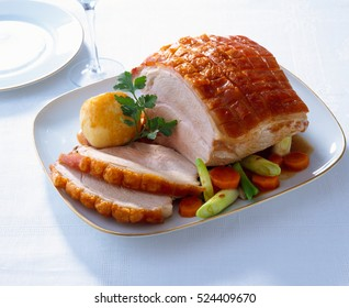 Roast Pork with crackling and vegetables on a plate, traditional German food