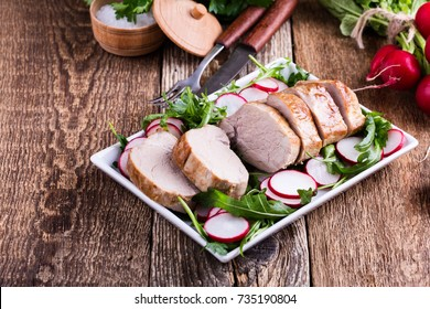 Roast pork fillet with with arugula and radish salad on white plate on wooden table