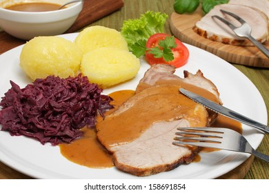 Roast pork with gravy, red cabbage and potato dumplings