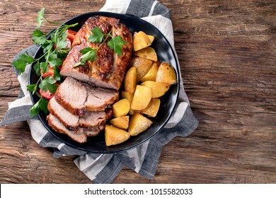 Roast pork with herbs and vegetables on rustic wooden table.