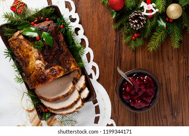 Roast pork loin with Christmas decoration. Top view. Wooden background.