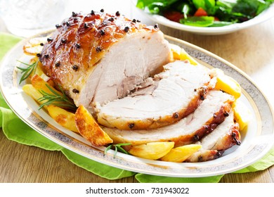 Roast pork with orange glaze, decorated with cloves.
