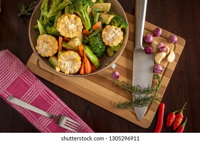 Roast vegetables, herbs and spices on chopping board with knife, food and cooking stock lay flat image.