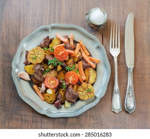 Roast venison with vegetables on a vintage pewter plates and old cutlery on a wooden table