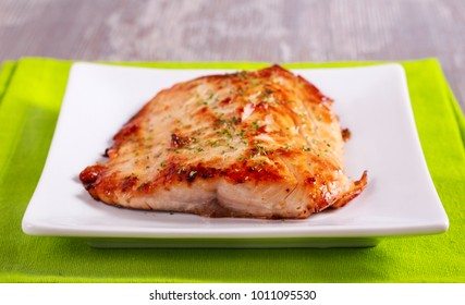 Roast white fish fillet on plate, top view