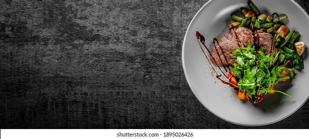 Roastbeef salad with green beans and mushroom in a bowl on Dark grey black slate background