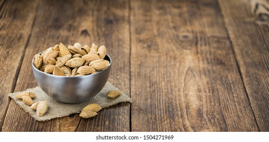 Roasted Almonds (in shell) on an old wooden table (close-up shot; selective focus)