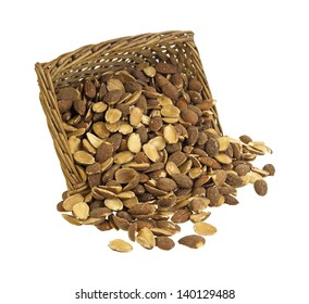 Roasted almonds that are spilling from an old wicker basket on to a white background.