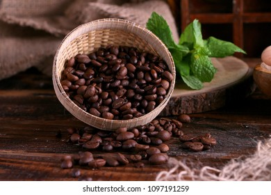 Roasted Arabica and Robusta Coffee beans in rattan bowl spread on wooden table in Rustic kitchen