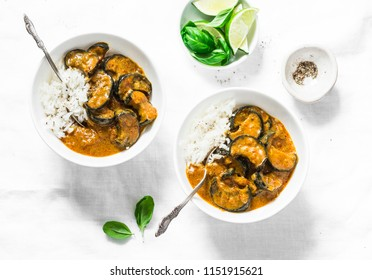 Roasted aubergine curry with rice on a light background, top view. Indian vegetarian cuisine. Flat lay
