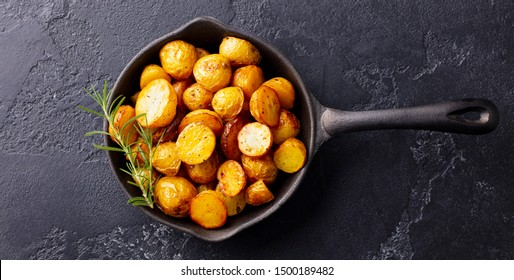 Roasted baby potatoes in iron skillet. Dark grey background. Top view.