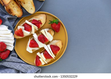 Roasted baguette slices with cheese and strawberries, gray textile serviette  on the gray background. Tasty breakfast idea