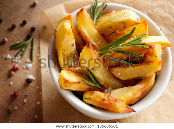 Roasted or baked potatoes with rosemary in a white bowl on wooden background - closeup rustic composition from above