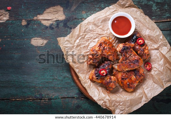 Roasted barbecue chicken wings with bbq sauce, italian herbs, olive oil and pepper, top view with copy space