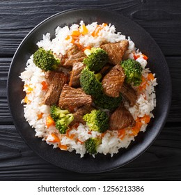 Roasted beef with broccoli with rice and persimmon side dish close-up on a plate on the table. top view from above
