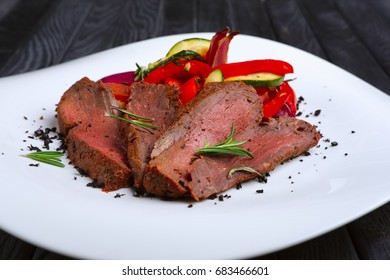 Roasted beef cutted on slices with grilled bell pepper, zucchini, onion and fresh rosemary