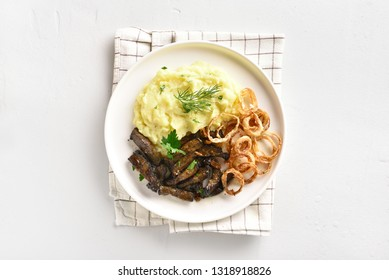 Roasted beef liver with mashed potatoes and fried onion rings on white plate over stone background with copy space. Pieces liver (offal) from beef with cooked vegetables. Top view, flat lay