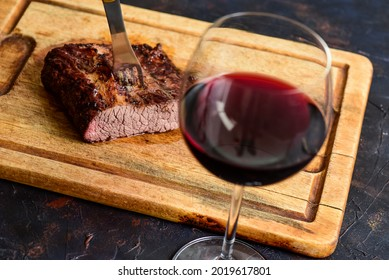 Roasted beef ribs with a glass of red wine presented on the table, traditional Argentine cuisine, Asado barbecue, Patagonia, Argentina.