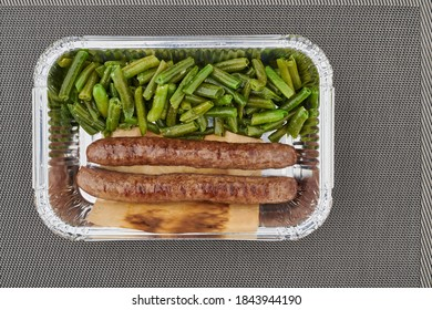 Roasted beef sausages with green beans in the metal bag with grey background.Tasty healthy dinner. Grilled meat with cooked beans for lunch.Seasoned delicious meat.Nutritious dish.Barbecue sausage.