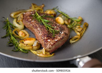 Roasted beef steak with onions, rosemary, pepper and salt