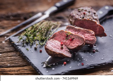 Roasted Beef steak with salt pepper thyme on rustic wooden table.