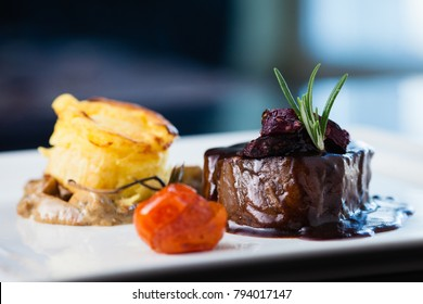 Roasted beef tenderloin with herb-potato muffin, mushroom ragout, baked tomatoes and rosemary-currant sauce