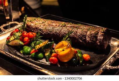 Roasted Beef Tenderloin  with herbs tied with a rope with cooking ingredients, oil and spices.