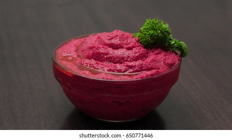 Roasted Beet Hummus in a Glass Bowl on a Wooden Background