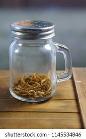 Roasted beetle larvae in a jar at sunset