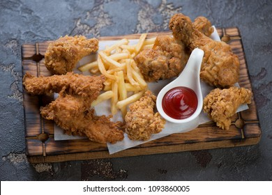 Roasted breaded chicken drumsticks, wings and fillet with french fries and sauce on a wooden serving tray, studio shot