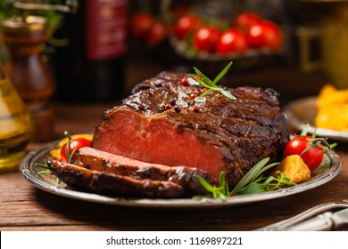 Roasted brisket. Rustic style, natural wooden background. Dark style. Front view.