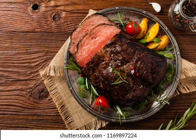 Roasted brisket. Rustic style, natural wooden background. Dark style. Top view. Flat lay.