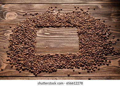 Roasted brown coffee beans on rough wooden table with blank copy space for text in form of rectangle