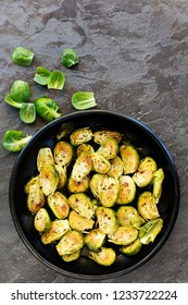 Roasted brussel sprouts in black bowl over slate.  Top view.