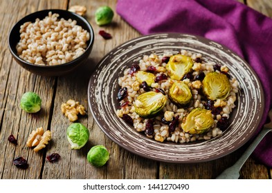 Roasted Brussels sprouts dried cranberries walnuts barley salad. toning. selective focus