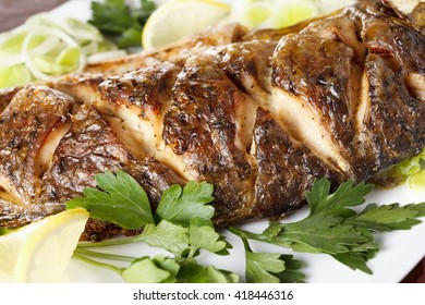 Roasted carp fish with vegetables entirely. Traditional Christmas menu. Closeup