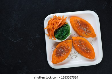 Roasted carrot cutlets served on a white plate, flatlay on a black stone background with copyspace, horizontal shot