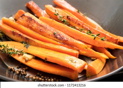 roasted carrots with thyme, coriander seed and honey in a wok pan,  recipe for root vegetables, selected focus, narrow depth of field
