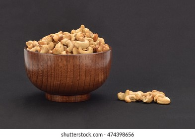 Roasted Cashew Nut in a Wooden Bowl with Dark Background