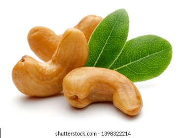 Roasted cashew nuts with green leaves isolated on white background