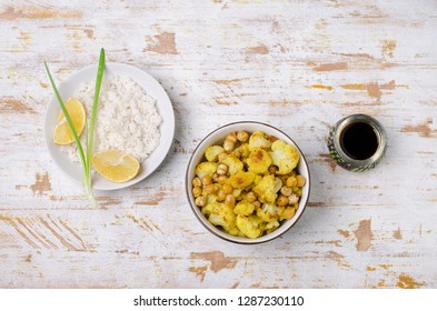 Roasted cauliflower with chickpeas and white rice on wooden background. Selective focus.