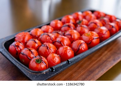 Roasted cherry tomatoes in a black metal baking dish. The cherry tomatoes are roasted with extra virgin olive oil and balsamic vinegar