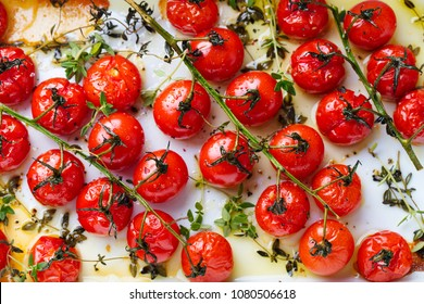 Roasted cherry tomatoes with herbs in baking dish. Top view. Food background.