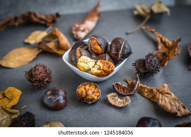 Roasted chestnut in a bowl on a table with leaves and chestnut spiky balls.
