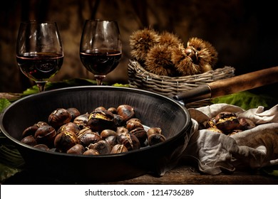 Roasted chestnuts in iron skillet on wooden table.