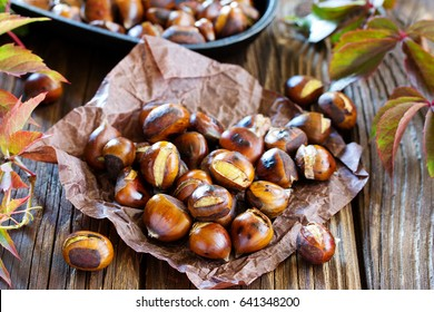 Roasted chestnuts on an old board. Selective focus.