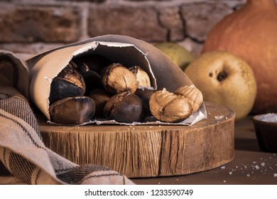 Roasted chestnuts in a paper cone, on a rustic kitchen countertop.