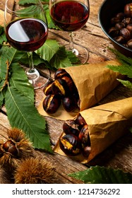 Roasted chestnuts in paper cones on wooden table.